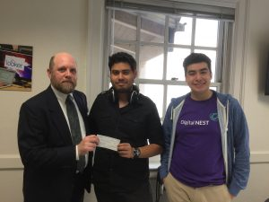 Steve Bean handing a check to Marcus Cisneros for his work laying out WQ. Next to him is cover and interior artist Nathan Campos.